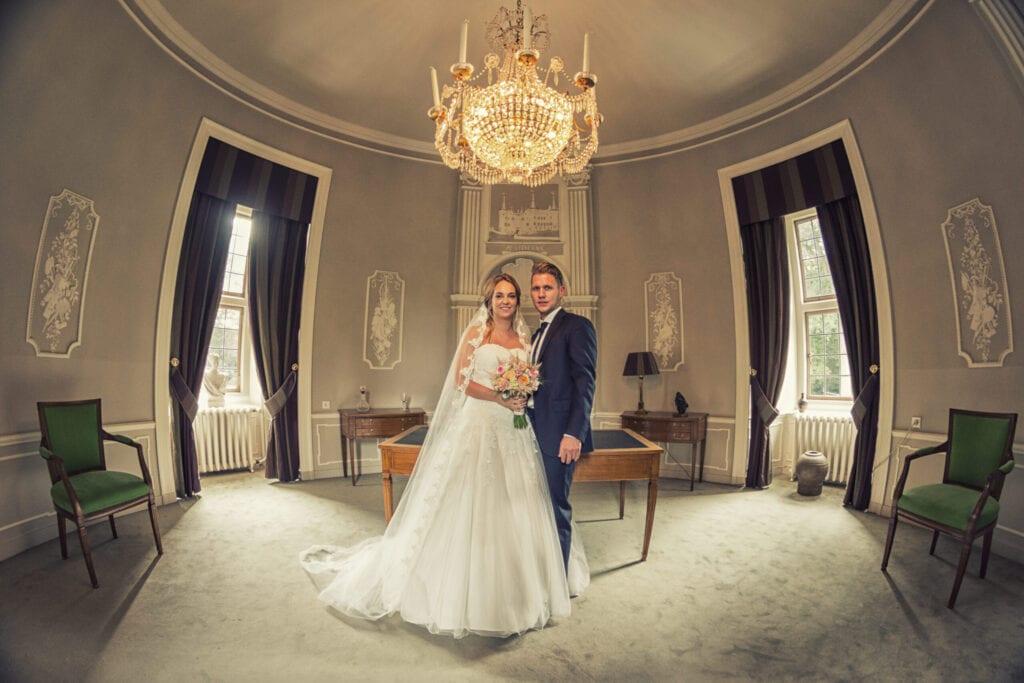 echtpaar poseert onder kristal kroonluchter