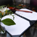 Coronavirus weddings marriage certificate pen and bouquet of white flowers on signing table.