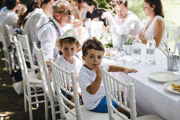 naming ceremony songs two preschool age boys posing for the camera sitting at a long white table