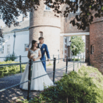 Dutch church weddings bride in white gown and groom in grey suit standing embrace at the gates of the castle