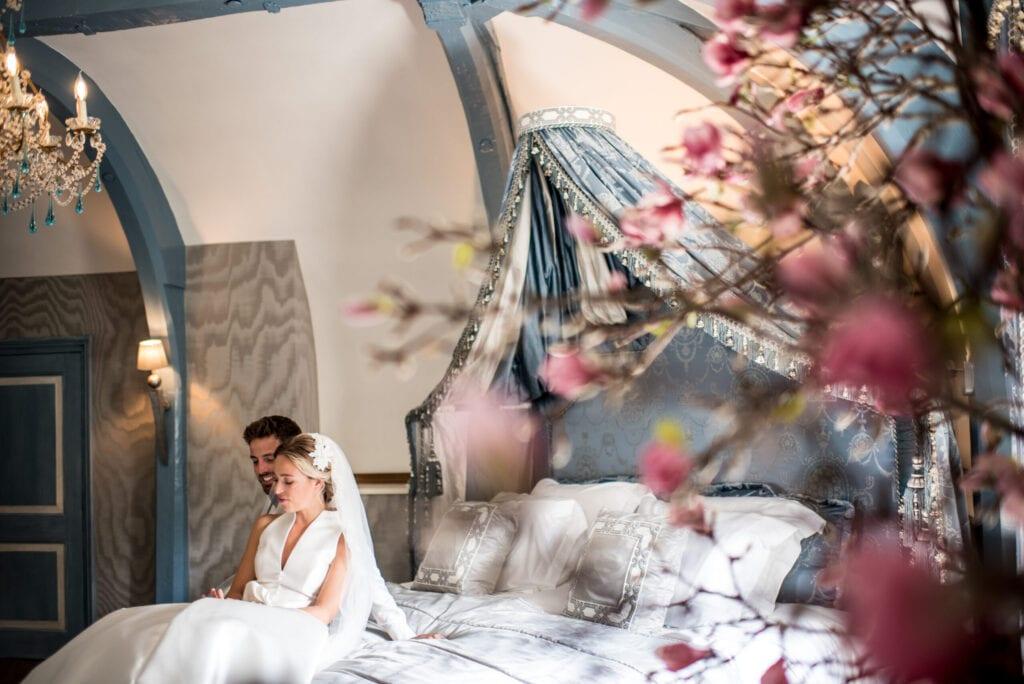 hippe bruiloft ideeën superluxe hotel zittend echtpaar op bed in bruidssuite op de eerste huwelijksnacht