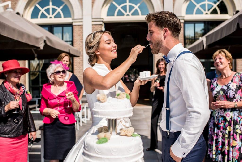 Trouwen in een orangerie bruidstaart gesnijden bruid neemt een stukje en voert dit aan haar man. taart gegeten en bubbels ingeschonken.