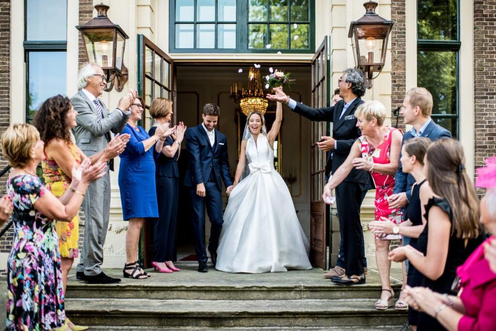 trouwen in een kasteel vrolijke echtpaar op de statige bordestrappen