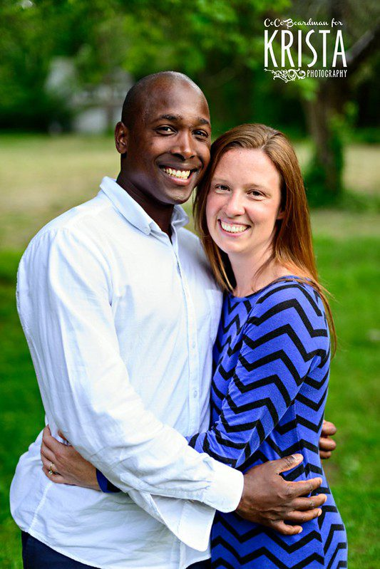 Wedding Ceremony Readings mixed-race couple black african man sitting in the grass with white caucasian woman smiling at one another
