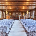 Dutch wedding planners wedding ceremony seating arrangement chairs draped in white linen and aisle floor runner
