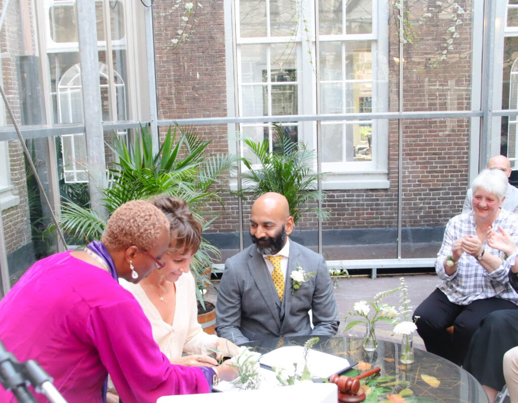 celebrant with wedding couple signing symbolic marriage certificate