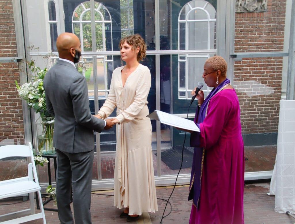 Corona maatregelen voor bruiloften trouwambtenaar met echtpaar die tegenover elkaar staan en hand in hand houden,