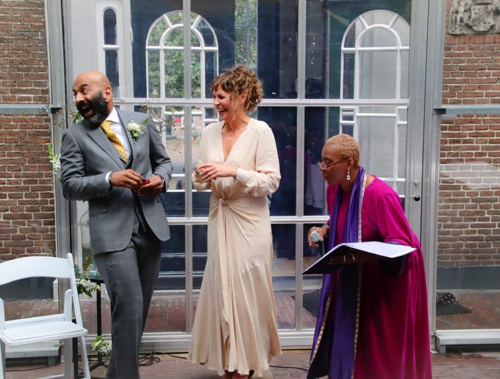 Corona maatregelen voor bruiloften lachende echtpaar met trouwambtenaar in de Kas