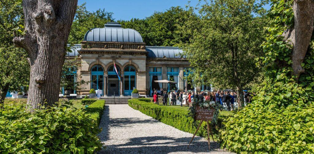 Trouwen in een orangerie bruidspaar met familie en vrienden arriveren bij Orangerie Elswout