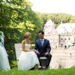 kasteel bruiloft Bruidspaar die heerlijk zitten genieten aan de waterkant tijdens trouwceremonie